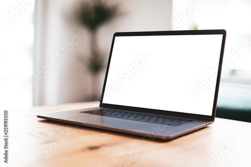 Fotografia  Laptop blank screen mockup on table in living room - front view