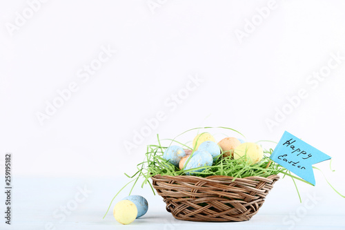 Foto  Colorful eggs in basket with text Happy Easter on white background