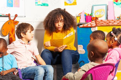 Fotografiet  Teacher in nursery school reading a book to kids