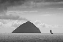Sailing Yacht Moving In Sea Near Ailsa Craig Against Cloudy Sky