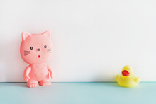 Rubber Toys On Blue And White Background. A Pink Rubber Cat And A Yellow Rubber Duck Standing Together. Bath Toys.