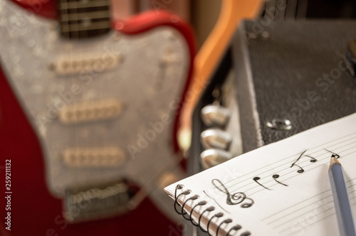 Fotografía  Composing music in a staff notebook with guitar and bass in the background