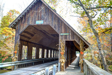 An Old Covered Bridge In Fall Decorated With Corn Stalks.