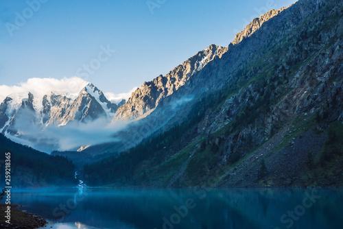 In de dag Ochtendgloren Ghostly forest near mountain lake in early morning. Mountain creek from glacier flows into lake. Mist on water surface. Low cloud among rock. Dark atmospheric misty wood landscape. Tranquil atmosphere