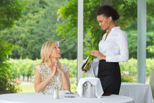 Woman Selecting A Bottle Of Wine In Restaurant