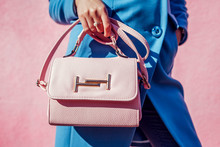 Young Woman Holding Stylish Handbag And Wearing Trendy Blue Coat. Spring Female Clothes And Accessories. Fashion