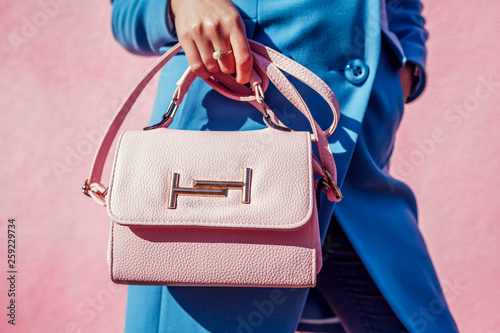 Young woman holding stylish handbag and wearing trendy blue coat Canvas Print