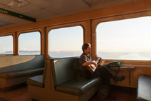 Happy, Smiling, Creative, Independent Middle Aged Man Solo Traveler Ferry Passenger Looking Out Window And Playing Guitar. Adventure, Fulfillment, Journey Concepts.