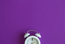 Flat Lay Of Small Alarm Clock On Purple Background