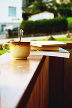 Reading Books And Drinking Morning Coffee At Balcony. Concept Of Lazy Sunday And Relaxing At Home.