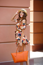 Stylish Brunette Girl Dressed In Short Multi-colored Dress And Hat Holding Orange Bag Walks In The City Street On A Sunny Day