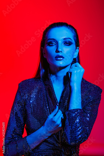 Fashion girl with long hair and stylish makeup in a black shining dress poses on the red background in neon light in the studio - 259236111