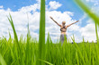 Relaxed healthy woman, arms rised, enjoying pure nature at beautiful green rice fields on Bali. Concept of healthy and clean environment, ecology, balance in life, freedom, happiness, and well being.