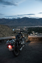 Motorcycle With Headlights On, Surrounded By Desert Town And Mountains