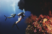 Two Women SCUBA Divers Next To A Coral Reef