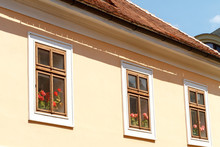 Geranium Behind Wooden Windows In A House With A Tiled Roof