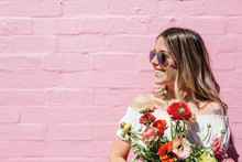Millennial Woman Smiling With A Bunch Of Flowers Against A Pink Brick Wall Background