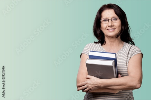 Fotografie, Obraz Mature woman teacher with books on background