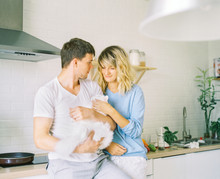 Couple Stroking Cat On Kitchen