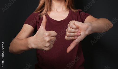 Photo  Woman showing THUMB UP and DOWN gesture in sign language on black background, cl