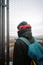Young Man From The Back Looks At The City Through The Grate