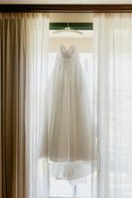 Elegant Wedding Gown Hanging In Window