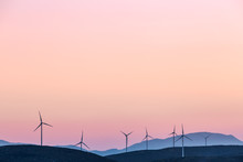A Series Of Wind Turbines At Sunset
