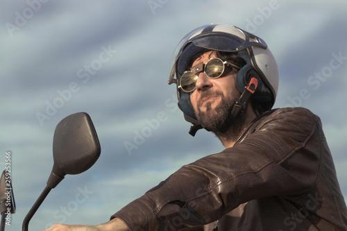 Fotografía  Brunette man with brown leather jacket on a motorbike