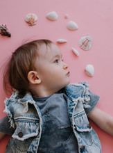 Profile Portrait Of Boy Posing On Pink Background With Seashells