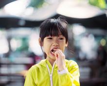 Asian Little Girl Eating Snack...