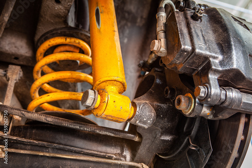 Photo Extreme closeup of yellow shock absorber underneath a car