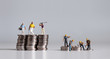 canvas print picture - Miniature people standing on a pile of coins. A concept of income disparity.