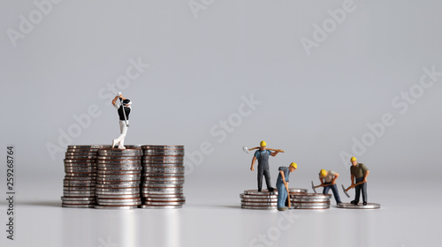 Fototapeta Miniature people standing on a pile of coins. A concept of income inequality. obraz