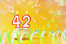 Forty Two Years Birthday. Cupcake With Burning Candles In The Form Of Number 42. Bright Yellow Background With Copy Space