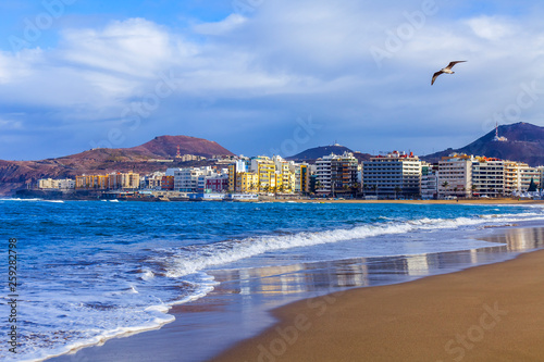 Las-Palmas de Gran Canaria, Spain, on January 8, 2018. The winter sun lights the Playa de Las Canteras beach on the bank of the Atlantic Ocean. beautiful embankment in the distance