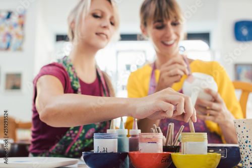 Canvas Print Two girl friends painting their own handmade ceramics