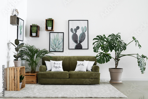 Interior of modern room with comfortable sofa and houseplants