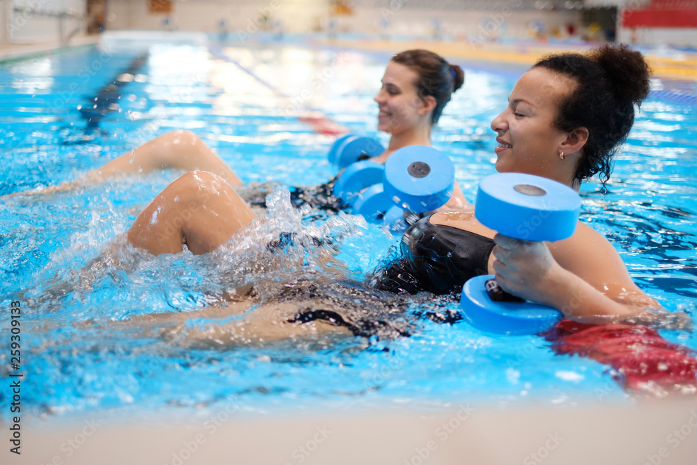 Fototapety, obrazy: Multiracial couple attending water aerobics class in a swimming pool