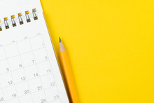 White Clean Calendar With Yellow Pencil On Solid Yellow Background With Copy Space Using As Reminder, Schedule Or Business Project Plan And Timeline Concept