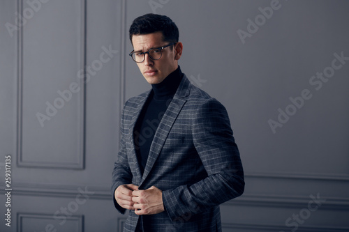 Handsome,fit man in gray suit with black turtleneck,black stylish eyeglasses looks confident at the camera Fototapeta