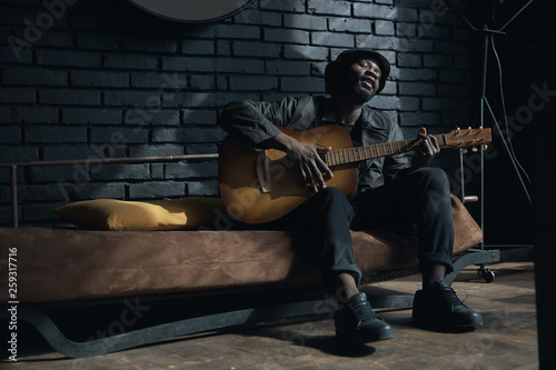 Musician in black trench coat and bucket hat sitting on bed and playing guitar Canvas Print