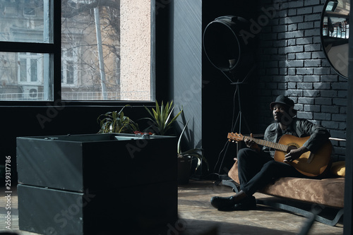 Musician in black trench coat and bucket hat sitting on bed and playing guitar. Songwriter in loft room. Fashion 2019 - 259317786