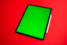 New IPad, Tablet On A Red Background With A Keyboard And Pen,  And Green Screen Top View