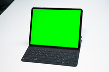 New IPad, Tablet On A White Background With A Keyboard And Pen, And Green Screen