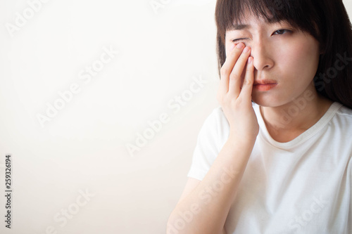 Tablou Canvas Asian woman suffering from eyes pain and feeling something in her eye