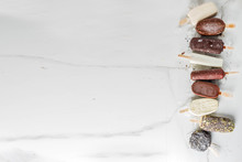 Assortment Of Various Popsicle Ice Cream, Vanilla And Chocolate, With Nuts, On A Dark Concrete Background With Ice, Copy Space Top View