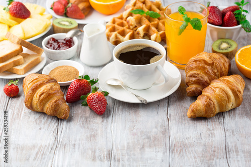 Photo Continental breakfast table with coffee, orange juice, croissants