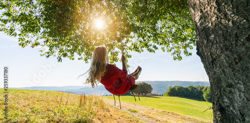 Photo  Unrecognizable girl in white dress swaying on a tree swing on peaceful evening