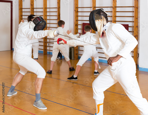 Joyful group practicing fencing techniques - Buy this stock
