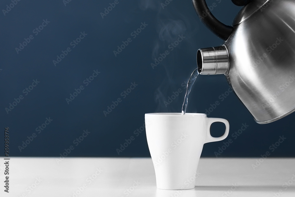 Fototapety, obrazy: Pouring hot water into into a cup on a dark background. cup of tea with steam. metal kettle